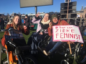 """Foto van de Women's March. Naomi Doevendans, Annika Mell en Tamar Doorduin zitten met z'n drieen naast elkaar in hun rolstoelen, hun ogen dichtknijpend tegen de zon. Annika maakt een peace-teken, Tamar en Naomi heffen hun vuist. Tamar houdt een protestbord vast met """"Ik ben een zieke feminist"""" erop, in grote roze letters."""