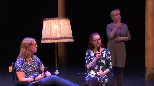 Tamar (links) en Eline (rechts) zitten op een podium, Tamar in haar rolstoel met de beensteunen omhoog, Eline op een stoel, haar stok tegen haar schoot aan geleund. Rechts achter Eline staat de gebarentolk. Tamar heeft schouderlang middenblond haar en draagt een bril, een donkerblauw bloemetjesshirt en een spijkerbroek. Eline heeft lang, half opgestoken kastanjebruin haar, een bruine bril en draagt een jurk met een grafisch patroon in wit en donkerblauw.