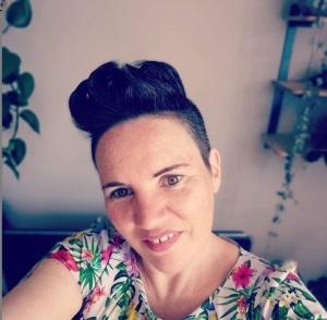 Foto van Xandra Koster. Xandra heeft een witte huidskleur en kort donkerbruin haar, opgeschoren aan de zijkanten en met een grote kuif bovenop. Ze glimlacht stoer maar ook enigszins bescheiden in de camera. Ze draagt een bloemetjesshirt in heldere kleuren. Op de achtergrand zijn kamerplanten te zien.