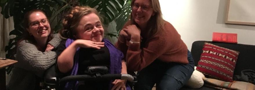 Eline, Mira en Tamar voor een grote kamerplant. Eline en Tamar leunen op de armleuningen van Mira's rolstoel en Mira houdt een hand onder haar kin.