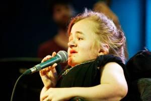 Foto van Mira tijdens een optreden. Ze draagt iets zwarts zonder mouwen, heeft rode lippenstift op en houdt een microfoon vast.