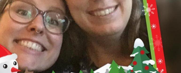 Grappige selfie van Eline en Tamar in een kitcherig kerstframe met een sneeuwpop en kerstbomen
