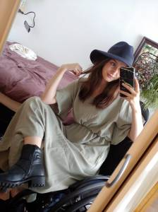 Foto van Birgit, een jonge, witte vrouw met lang lichtbruin haar, poserend in hippe kleren en een hoed vóór haar bed